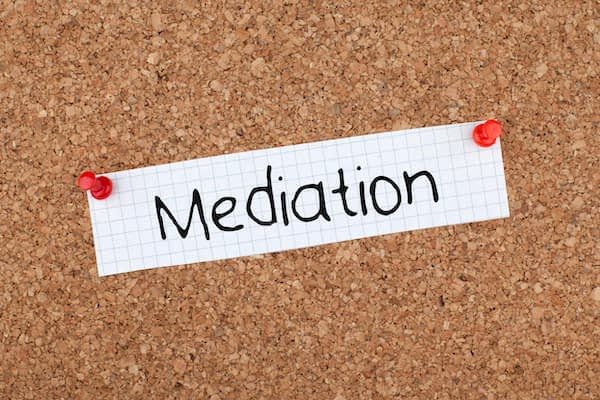 Image of the word Mediation on a note pinned to a bulletin board.